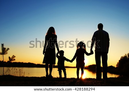 silhouette family, including his father, mother and two children in the hands of - stock photo
