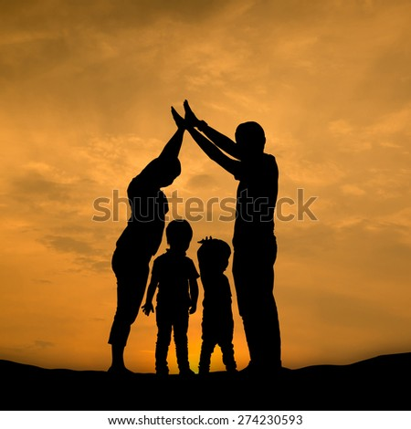 Silhouette Family ,prarents cover two son in sun set.