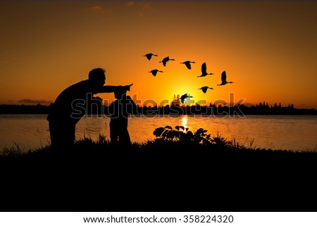 silhouette father and son play binoculars sunset background