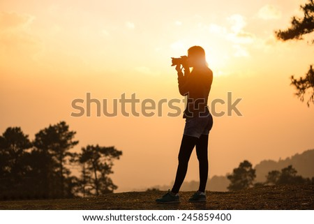 Silhouette female photographer taking a picture with the sun behind - stock photo