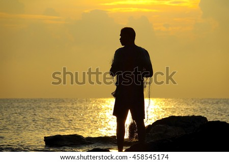silhouette fisherman working on beach at lake on sunrise time,select focus with shallow depth of field. - stock photo