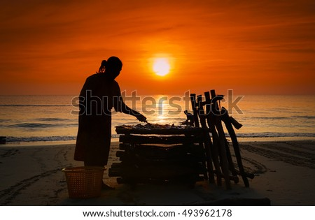 silhouette fisherman working  on beach on sunrise time at Songkhla Southern Thailand:select focus with shallow depth field,ideal use for background.