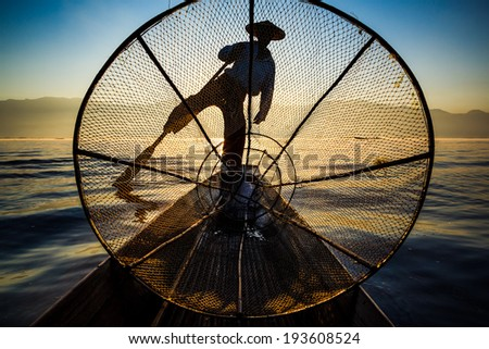 Silhouette fishermen in Inle Lake at sunrise, Inle, Shan State, Myanmar - stock photo