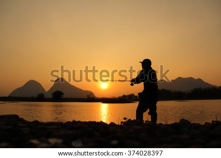 Silhouette fishing during sunrise