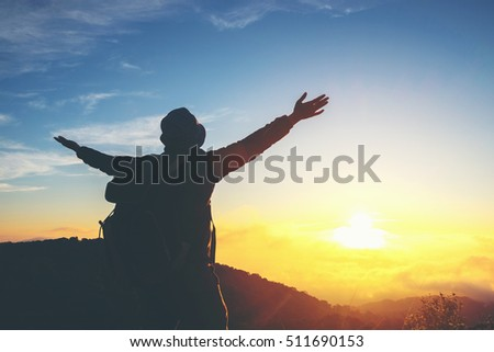 Silhouette Freedom man standing with raised arms and enjoying on time