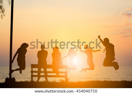 Silhouette friends jumping with joy and happiness over blurred, sand and sea. They love each other as longtime friends. I promise not to leave each other. Concept friends. concept happy. - stock photo