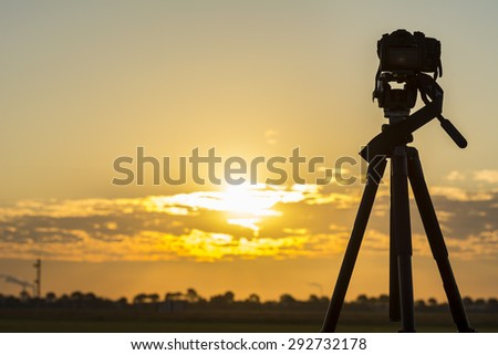 Silhouette from a recording camera on a tripod during sunrise - stock photo