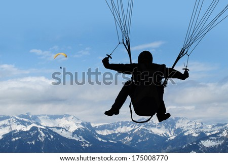Silhouette from paraglider in the air above the european alps, another person is paragliding in the background. - stock photo
