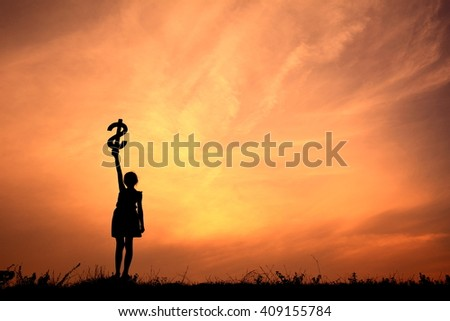 Silhouette girl holding money in the sunset.
