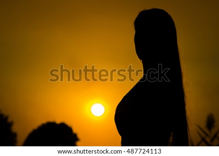 Silhouette girl on the nature looks at the sun at sunset