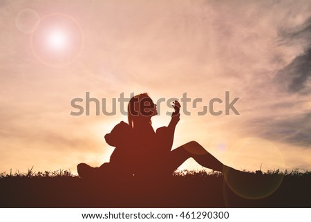 Silhouette girl playing musical with teddy bear at sunset