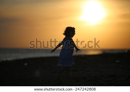 Silhouette girl sunset kid playing sea - stock photo