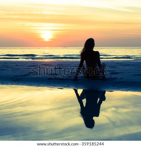 Silhouette girl with long hair on the beach during sunset, with reflection in the water. - stock photo