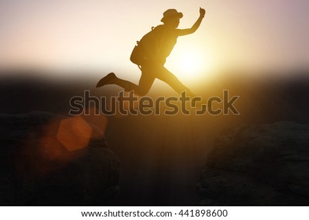 Silhouette girl with the leap over the cliff through difficulties, and excessive to success. in the sunset. Concept big dream to success.