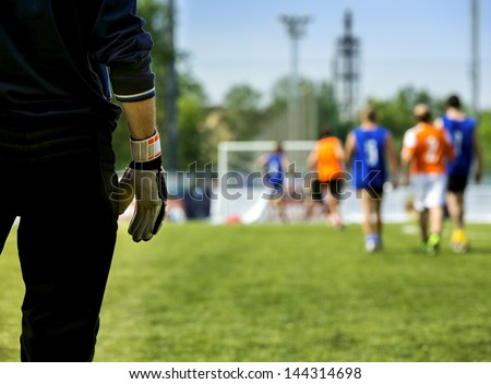 Silhouette goalkeeper standing  in ready position at gate on background of playing team. Gloves closeup , rear view - stock photo