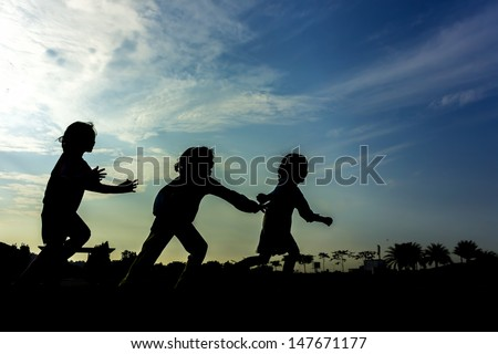 Silhouette group of happy children playing at park