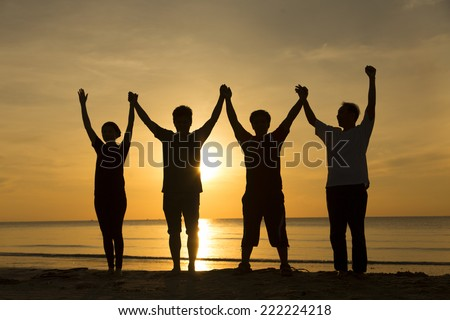 Silhouette group of people at the beach  - stock photo