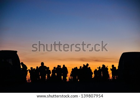 Silhouette group of tourists and natural backdrop - stock photo