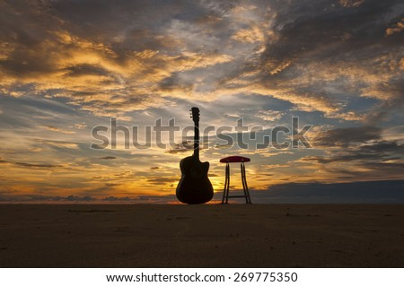 Silhouette Guitar with Chair at The Beach During Sunset Moment Image has grain or blurry or noise and soft focus when view at full resolution.  (Shallow DOF, slight motion blur)  - stock photo