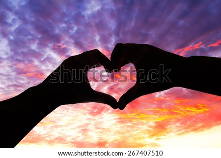 Silhouette hand in heart shape and beautiful sky - stock photo