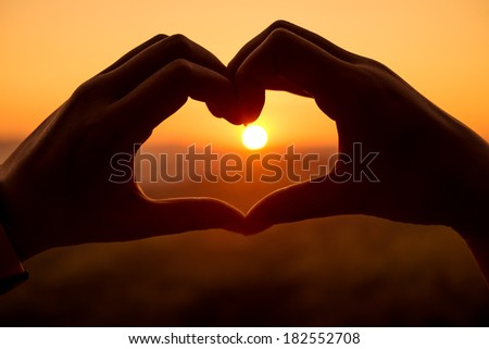Silhouette hand in heart shape with sunrise in the middle - stock photo