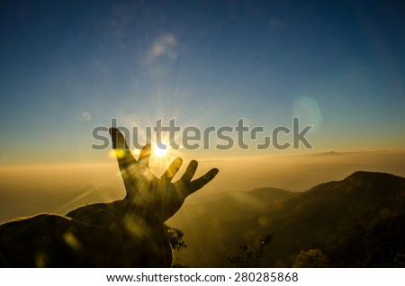 Silhouette hand to sun, Sunrise scene with mountain and sea of mist - stock photo