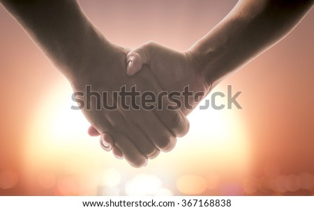 Silhouette handshake symbol forming a heart over orange sky background. World Cancer Day, We Can, I Can, Trust, Love, Beginning, Happy Valentine's, Business, CSR, Solidarity, Unity, Synergy concept. - stock photo