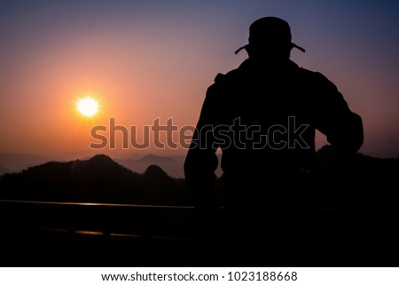 Silhouette Handsome man looking forward with binoculars at a mountain and drinking coffee.