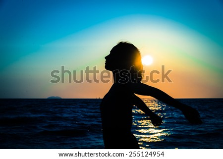 Silhouette happiness young woman on the beach and sea at sunset times - Vintage color processing style pictures - stock photo
