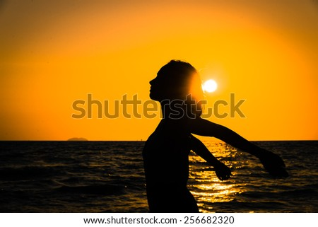 Silhouette happiness young woman on the beach and sea at sunset times - Vintage color processing style pictures