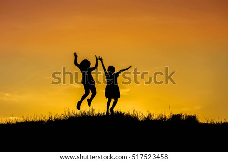 silhouette happy children jumping to sky on sunset. happy time concept