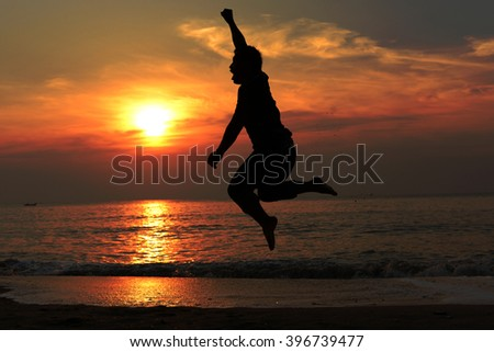Silhouette happy man jump on the beach with sun