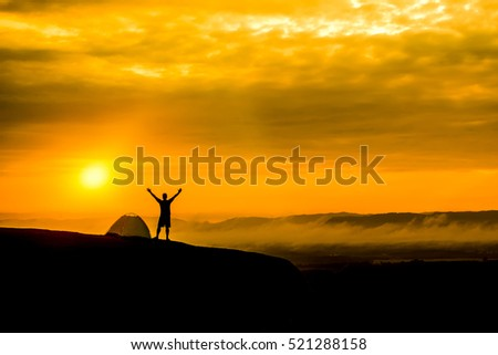 Silhouette Happy young man with a tent, on the rocks.On Sunrise