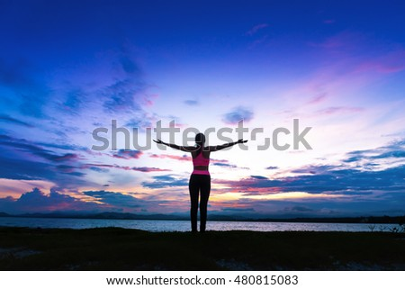 Silhouette healthy woman doing exercises on the beach behind colourful sky at Phuket,Thailand