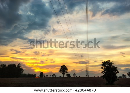 Silhouette high voltage electricity pylon at time sunset - stock photo