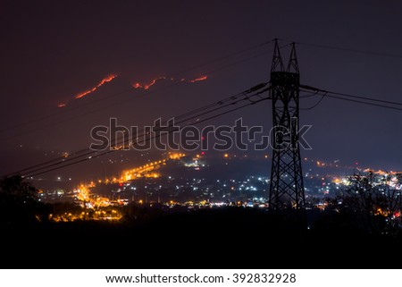 silhouette high-voltage tower electricity line on city light background and wildfire on mountian - stock photo