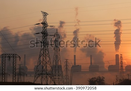 Silhouette high voltage transmission line and smoke from coal power plant background, Industry pollution - stock photo