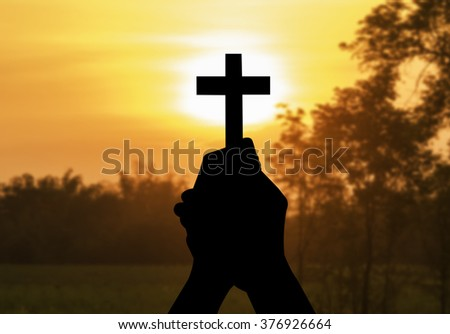 silhouette human hands holding a cross holy and prayed for blessings from God whit blur the background of the sunset.  Amour Worship God concept.
