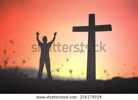 Silhouette human raising hands over the cross on nature background. - stock photo