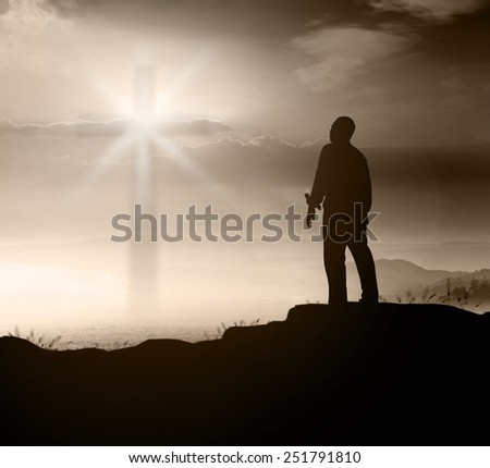Silhouette human standing over blurred the cross on nature background. - stock photo