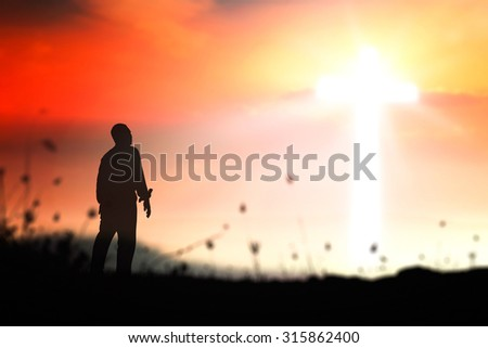 Silhouette human standing over blurred the cross with amazing light on beautiful autumn sunset background.