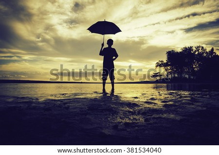 silhouette image concept a boy standing and hold an umbrella at the beach with beautiful sunrise sunset background. dramatic cloud and reflection on sandy beach - stock photo