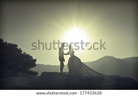 Silhouette image of a bride and groom by the beach at sunset - vintage photo - stock photo