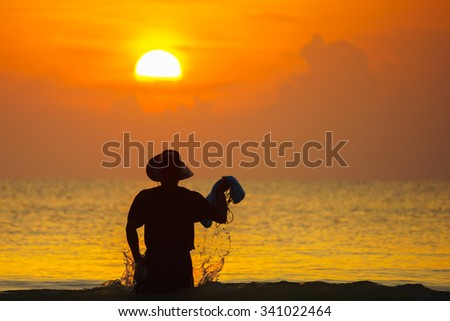 Silhouette image of fisherman with sunrise background in the morning.Close up and selective focus with shallow depth of field. - stock photo
