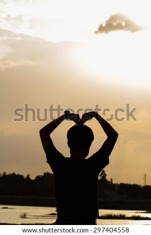 Silhouette Image of Man Raising His Hand Showing  - stock photo
