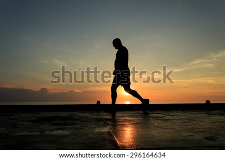 Silhouette Image of man walking on the helideck in the evening for excercising