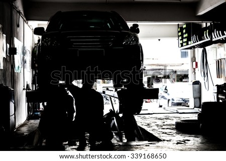 Silhouette image of mechanics inspecting cars suspended on platform in a very small and tight workshop - stock photo