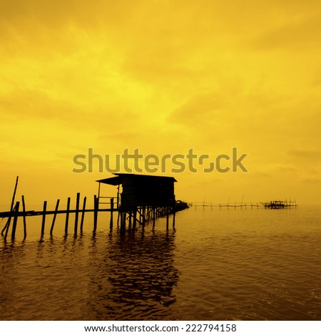 silhouette image of the jetty and houseboat during golden hour