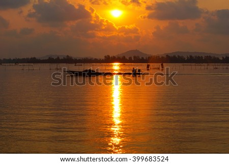 Silhouette image view in dark tone colorful sunrise reflection lighting water on lake in the morning:select focus with shallow depth of field:ideal use for background. - stock photo
