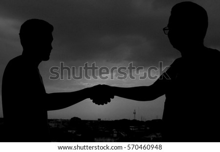 Silhouette In Black And White Men Shaking Hands